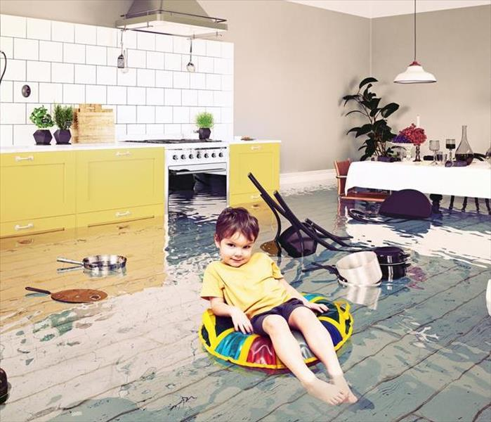 A little boy sitting in a float in a kitchen that has standing water.