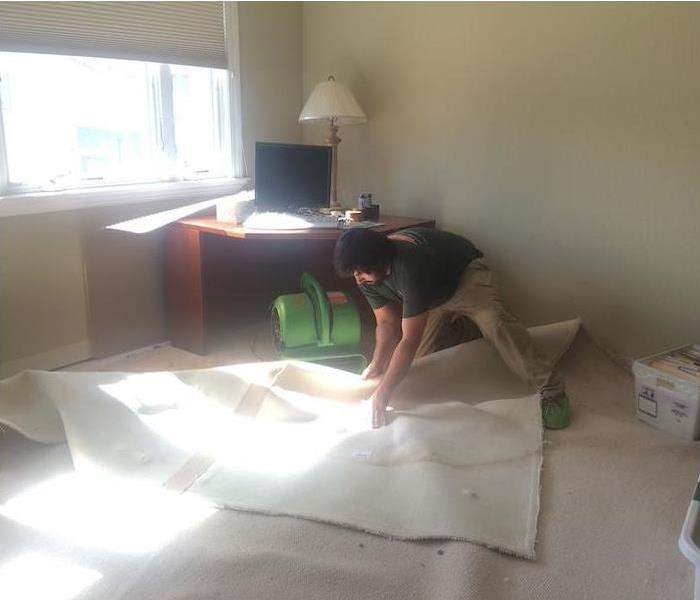 SERVPRO Technician pulling back carpet to dry